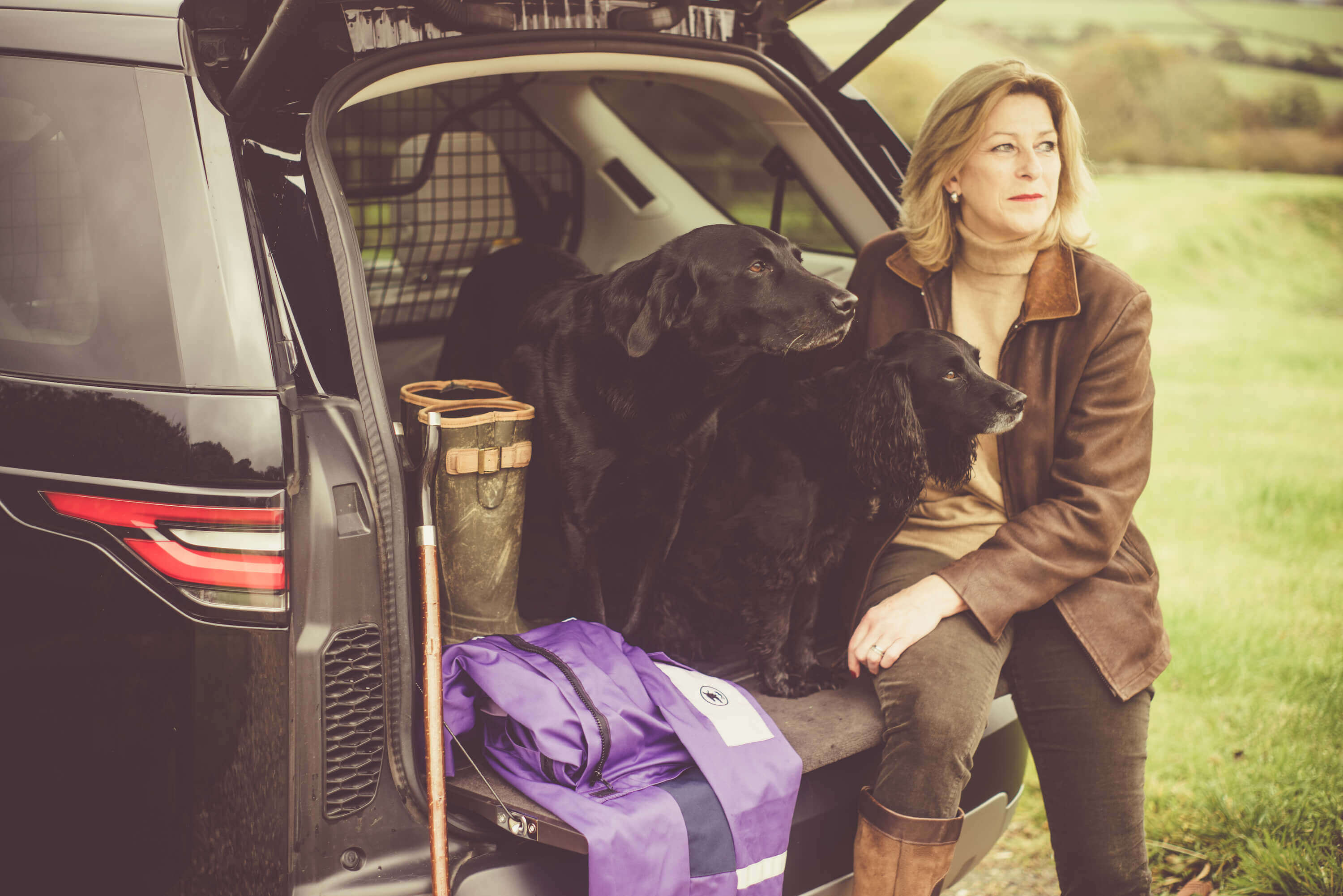 woman at the back of the car holding two black dogs