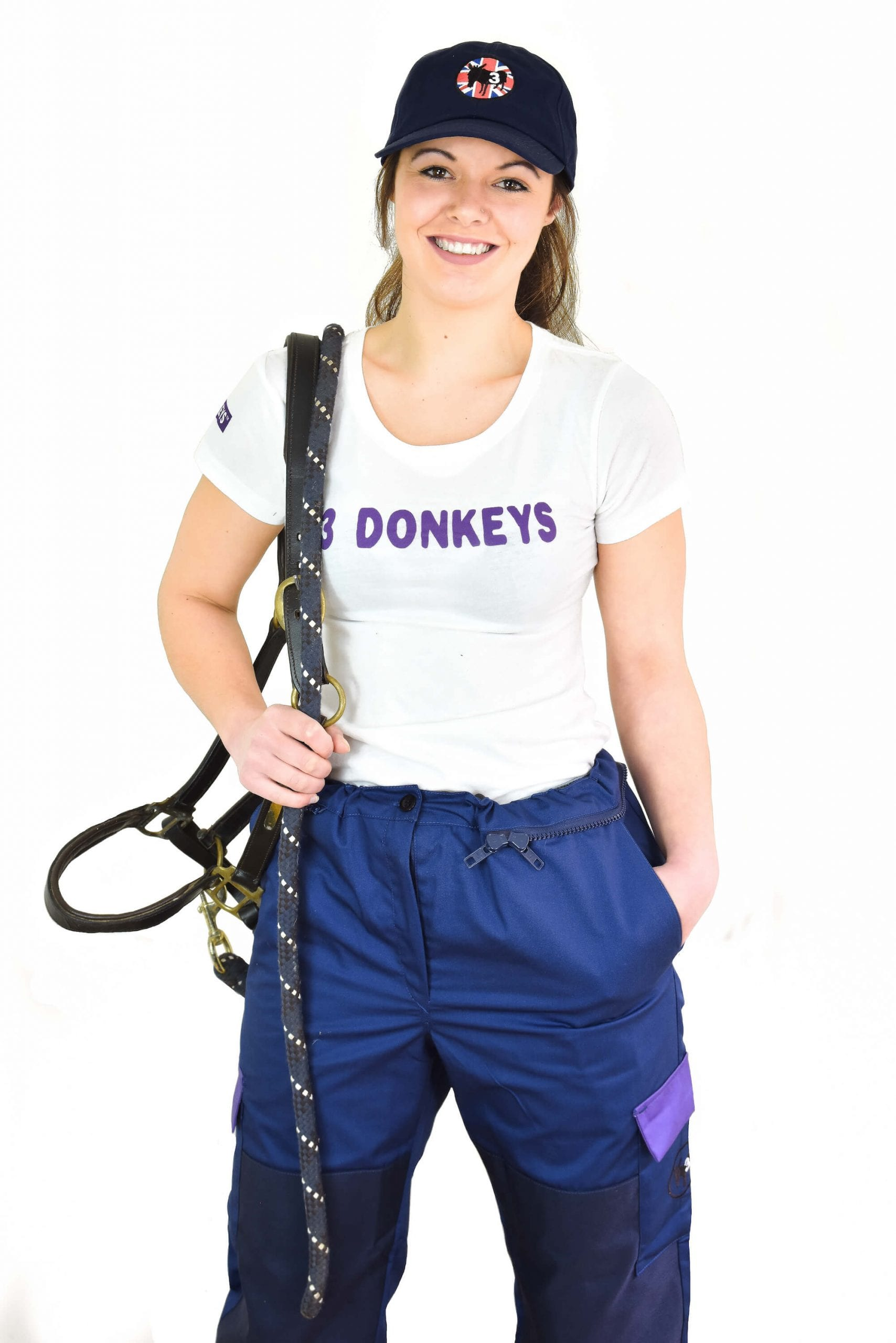 a girl wearing white t-shirt and blue coverall with a climbing harness