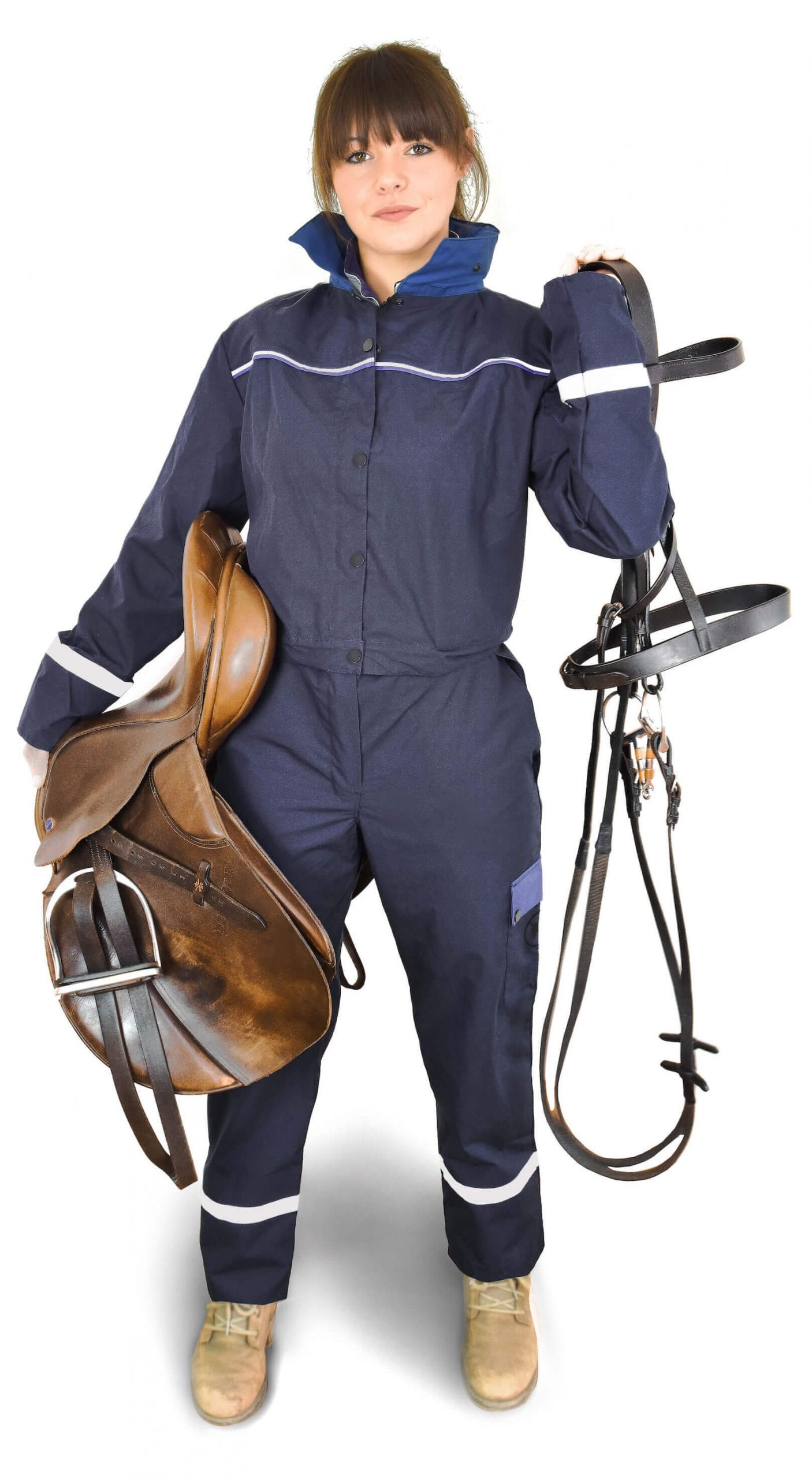 a girl wearing classic blue coverall holding horse saddle and climbing harness
