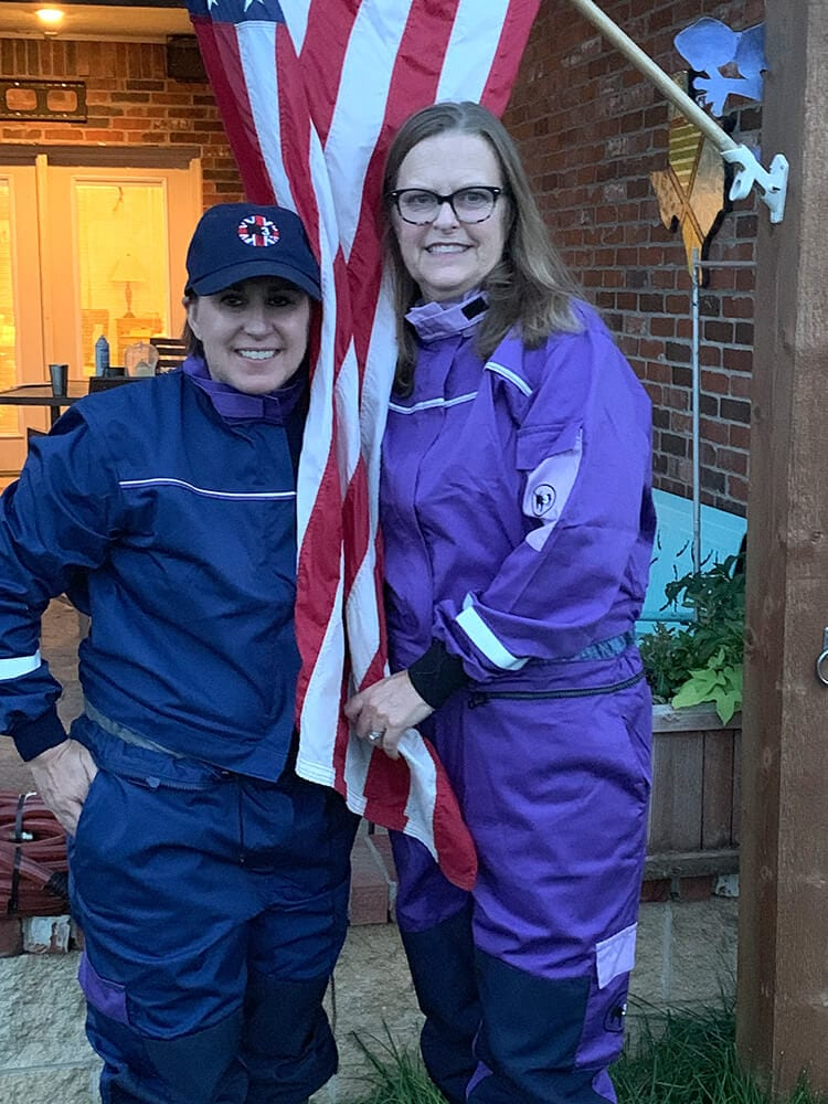 two women wearning classic blue and purple coveralls centered with the american flag